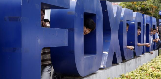 Napis przed fabryką Foxconn w Shenzen, Chiny, gdzie firma zmaga się z plagą samobójstw wśród pracowników