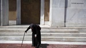 Grecja: Żebraczka przed gmachem banku centralnego w Atenach
